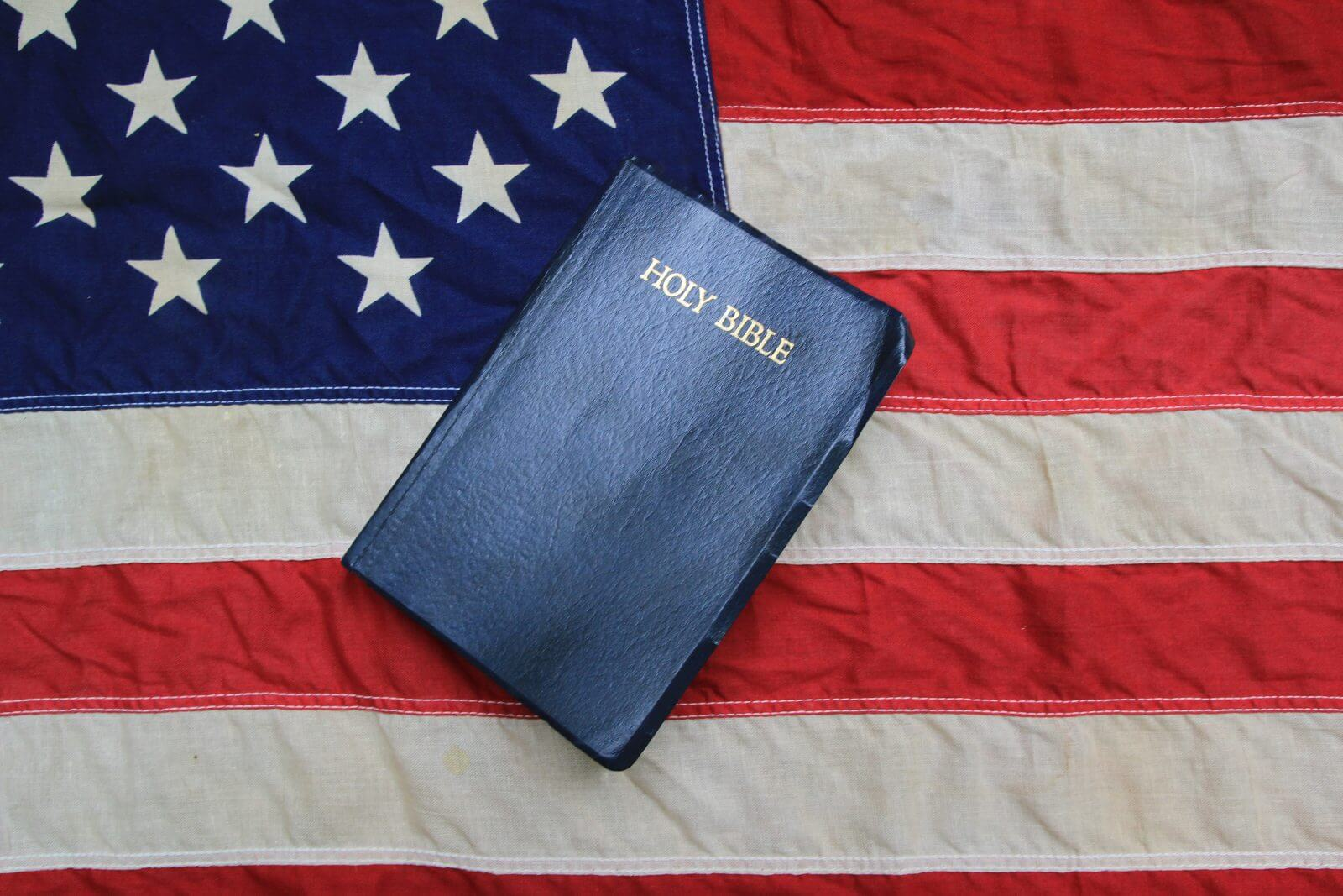 King James Bible surrounded by bullets with American Flag as the background.